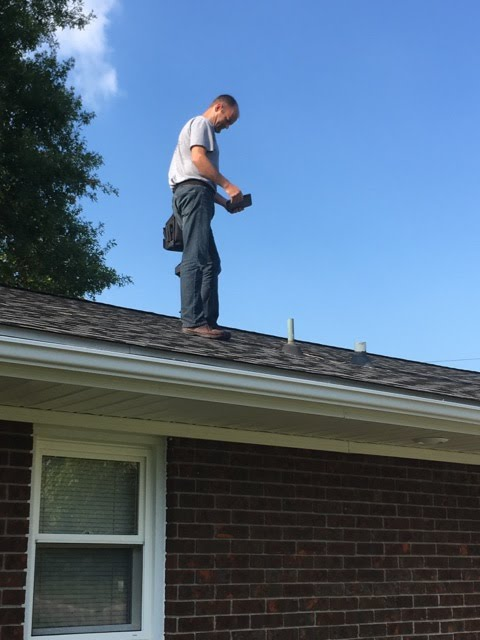 Mat inspecting a roof of a home.